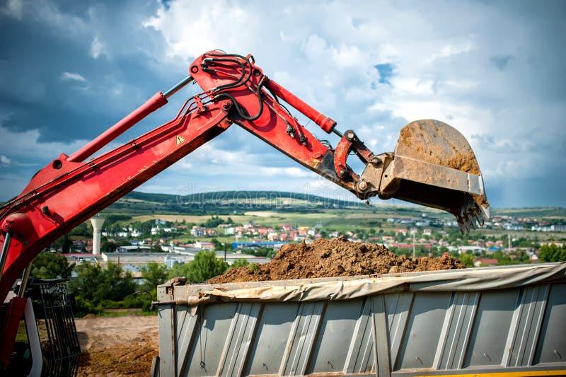 Primo piano dell'escavatore industriale che carica un autocarro con cassone ribaltabile fotografia stock