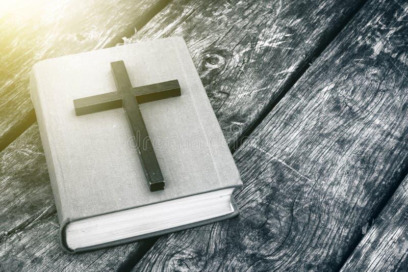 Primo piano dell'incrocio cristiano di legno sulla bibbia sulla vecchia tavola immagine stock libera da diritti