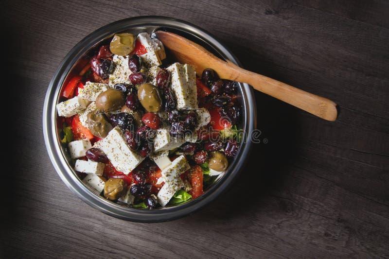 Primo piano dell'insalata gastronomica deliziosa del feta delle olive e del pomodoro spruzzata con le spezie delle erbe in una ci immagini stock