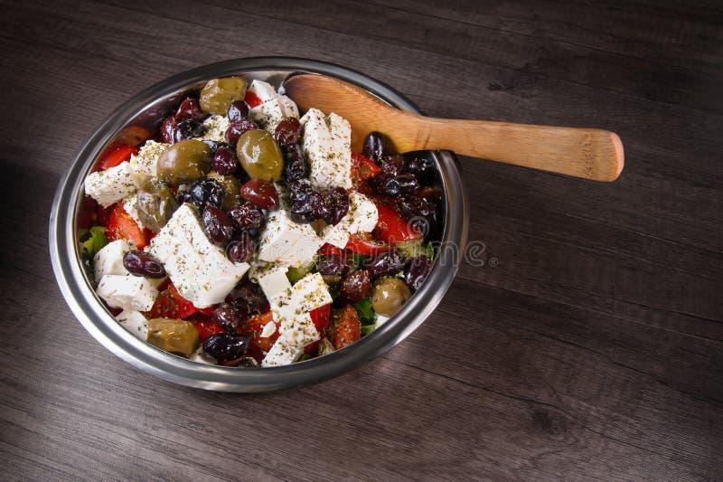 Primo piano dell'insalata gastronomica deliziosa del feta delle olive e del pomodoro spruzzata con le spezie delle erbe in una ci fotografia stock