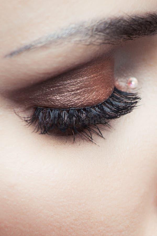 Primo piano dell'occhio della donna con ombretto marrone fotografia stock libera da diritti