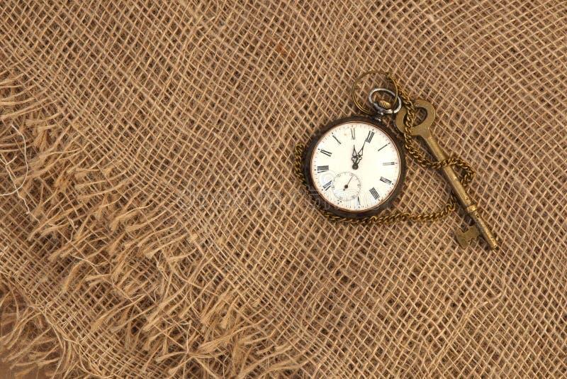 Primo piano dell'orologio antico e della chiave su vecchia tela di sacco Tempo che passa concetto Concetto storico di studi immagine stock libera da diritti