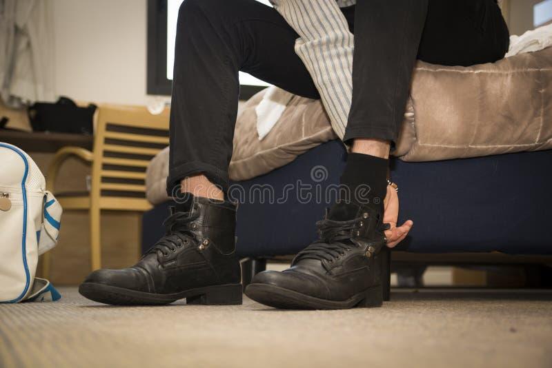 Primo piano dell'uomo a casa che mette sulle scarpe fotografia stock