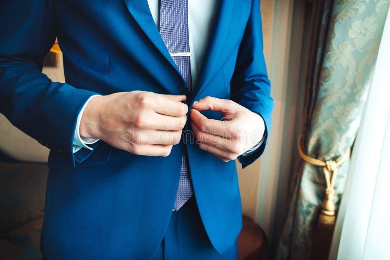 Primo piano dell'uomo che abbottona il suo rivestimento, concetto dell'abbigliamento di affari immagine stock