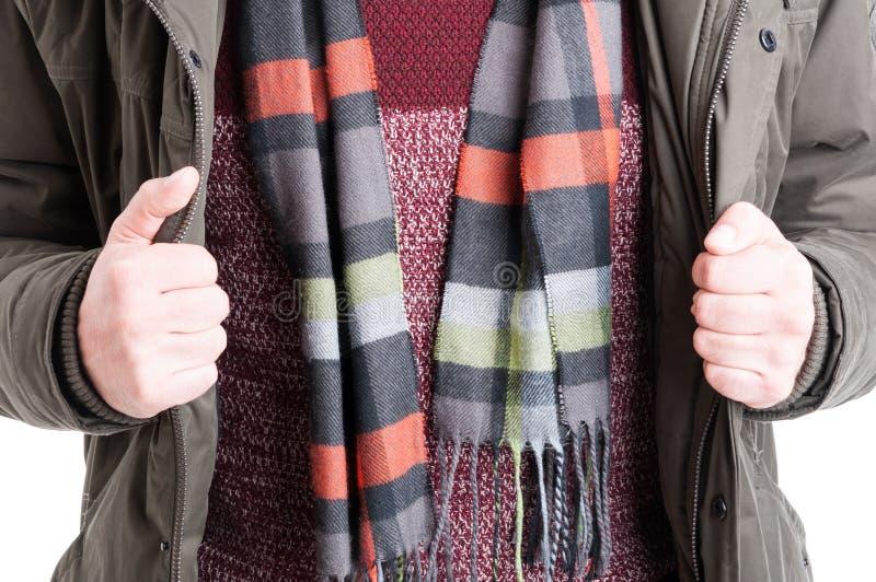 Primo piano dell'uomo che mostra il maglione ed il rivestimento del piumino immagine stock libera da diritti