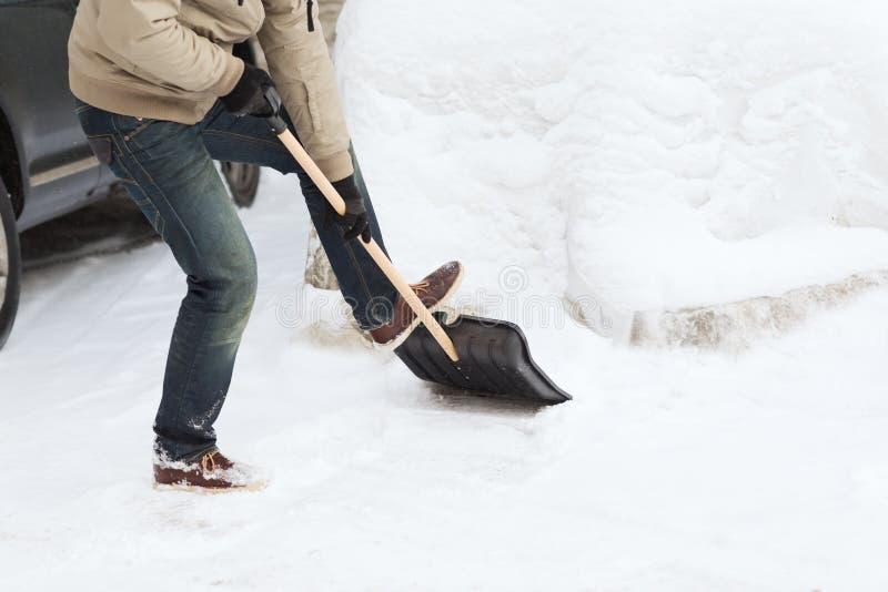 Primo piano dell'uomo che spala neve dalla strada privata fotografia stock libera da diritti