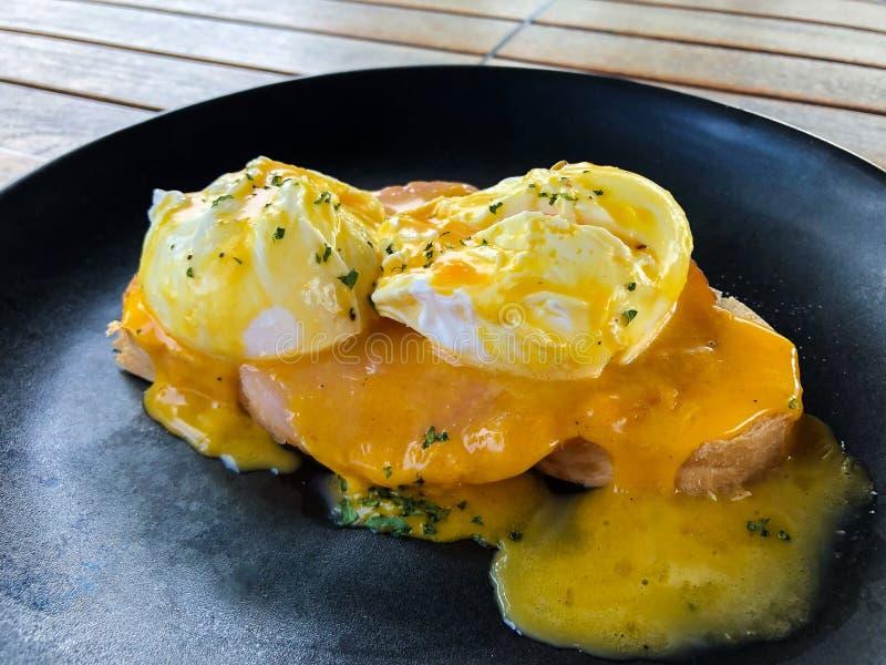 Primo piano dell'uovo alla benedict con il prosciutto ed il pane tostato francese su una banda nera per la prima colazione fotografia stock