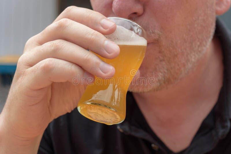 Primo piano della birra bevente dell'uomo da un vetro immagine stock libera da diritti