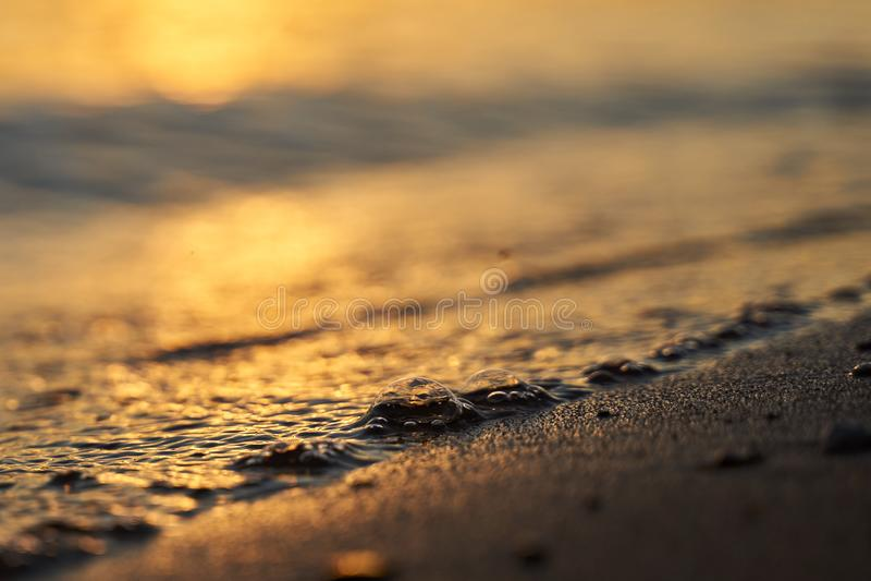 Primo piano della bolla dell'acqua dalle onde sulla costa sabbiosa al tramonto Fondo dorato di ora immagini stock libere da diritti