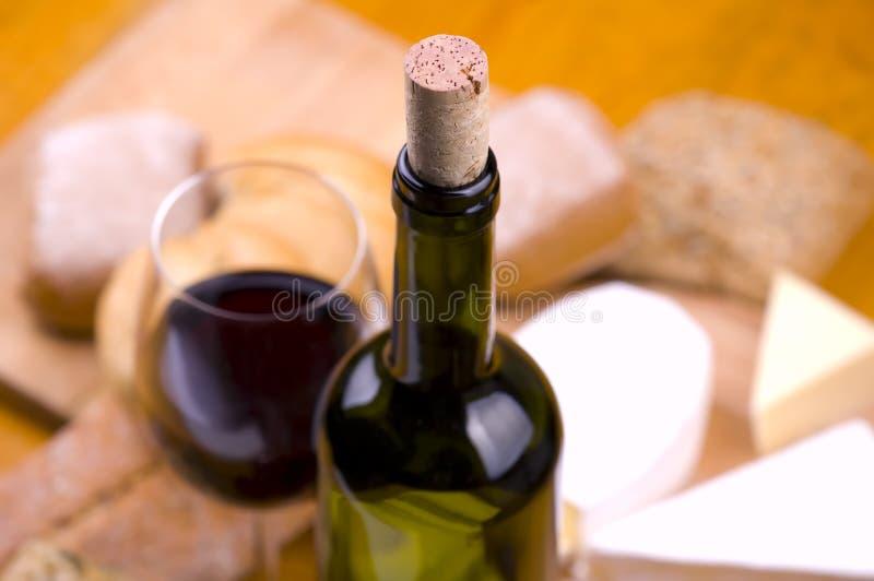 Primo piano della bottiglia di vino con alimento e vetro fotografia stock