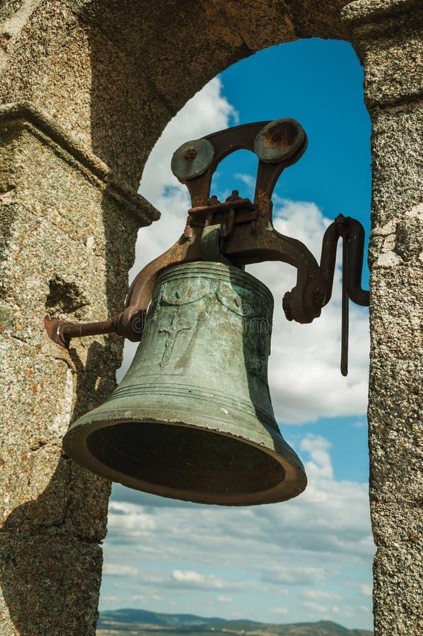 Primo piano della campana bronzea sopra la parete al castello di Trujillo fotografia stock