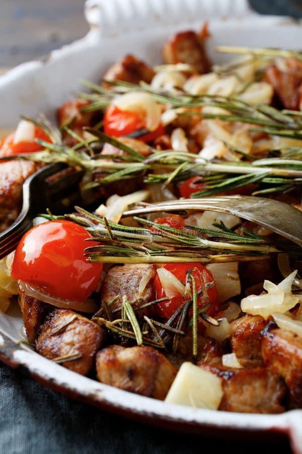 Primo piano della carne dell'arrosto Roasted con i pomodori e le spezie sulla pentola immagine stock