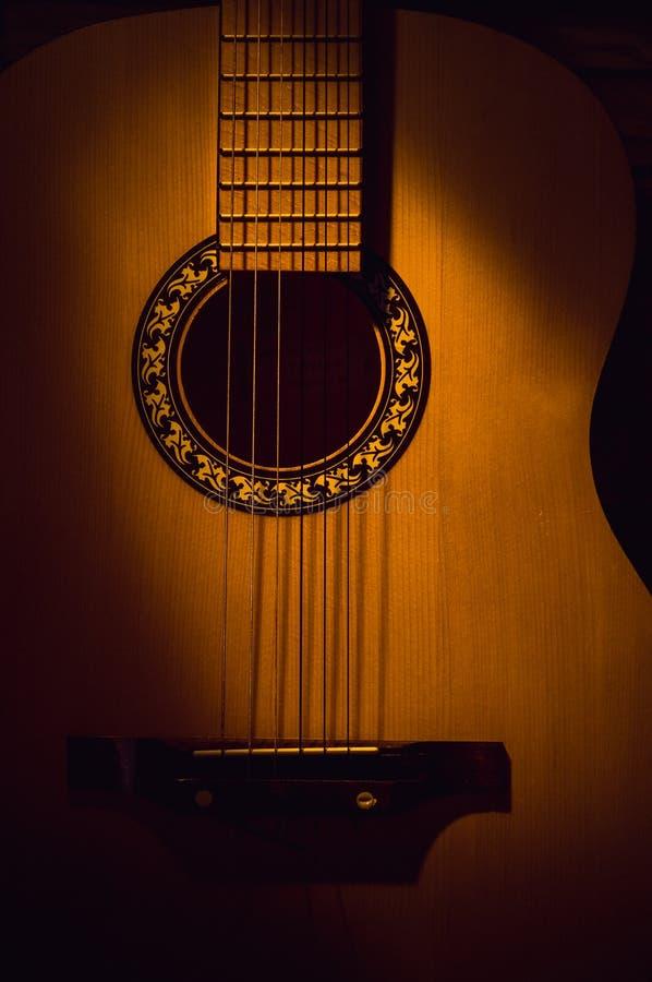 Primo piano della chitarra acustica nello scuro, illuminato da un fascio luminoso fotografia stock