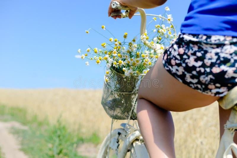 Primo piano della coscia della giovane signora sulla bicicletta con immagine stock libera da diritti