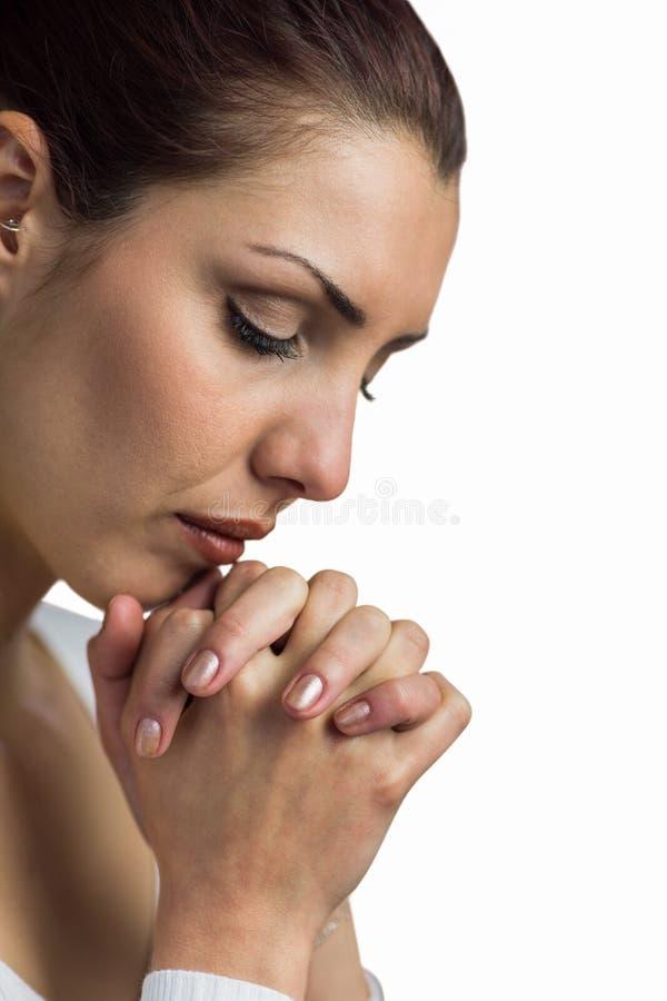 Primo piano della donna che prega con prender per manosi e degli occhi chiusi immagini stock