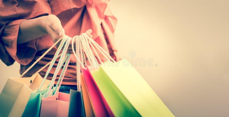 Primo piano della donna che tiene il sacchetto della spesa della carta di colore alla via Vendita di estate e concetto di acquist fotografia stock