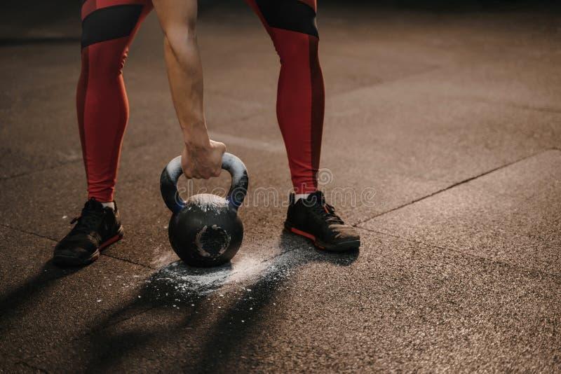Primo piano della donna di sport che tiene kettlebell mentre addestramento del crossfit Pesi pesanti di sollevamento femminili fotografia stock