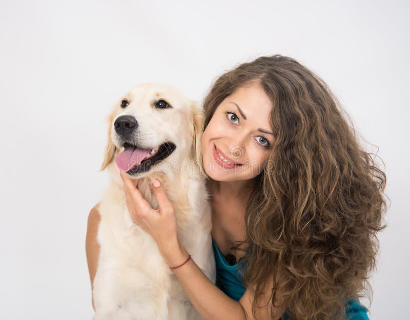 Primo piano della donna femminile che smilling e che esamina macchina fotografica con il suo cane isolato su bianco fotografia stock