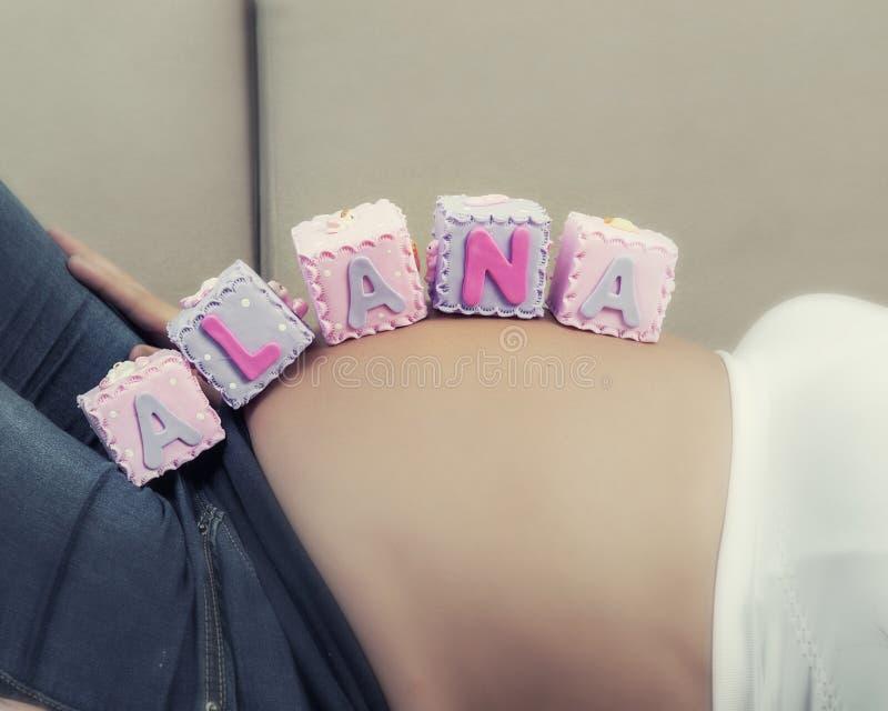 Primo piano della donna incinta irriconoscibile con il nome Alana sulla sua pancia fotografie stock
