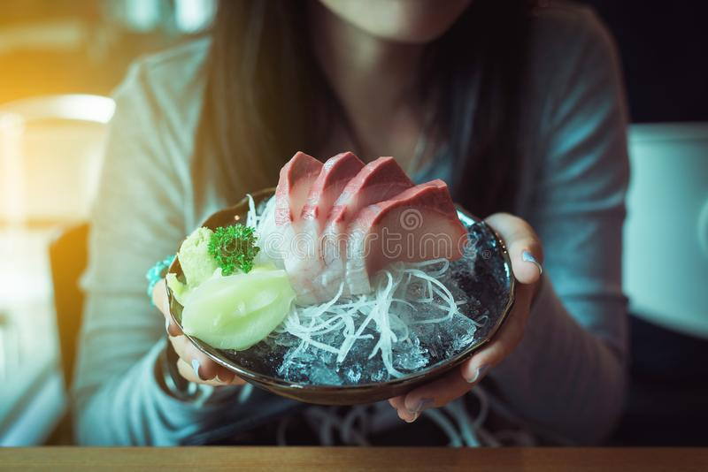 Primo piano della donna della mano che tiene l'insieme di Tuna Hamachi, alimento giapponese nel Giappone tradizionale immagine stock