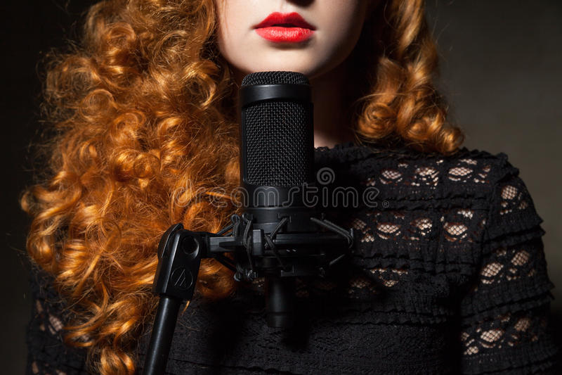 Primo piano della donna riccio-dai capelli con il mic immagine stock libera da diritti
