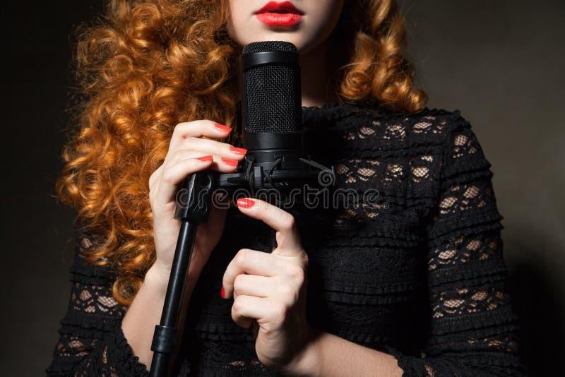Primo piano della donna riccio-dai capelli con il mic fotografia stock libera da diritti