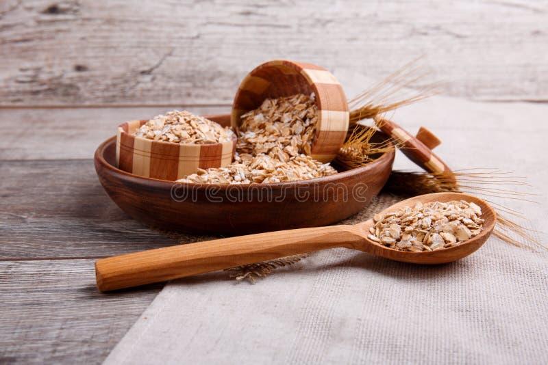 Primo piano della farina d'avena cruda in una ciotola con un cucchiaio di legno pieno della farina d'avena, su una tavola di legn fotografia stock libera da diritti