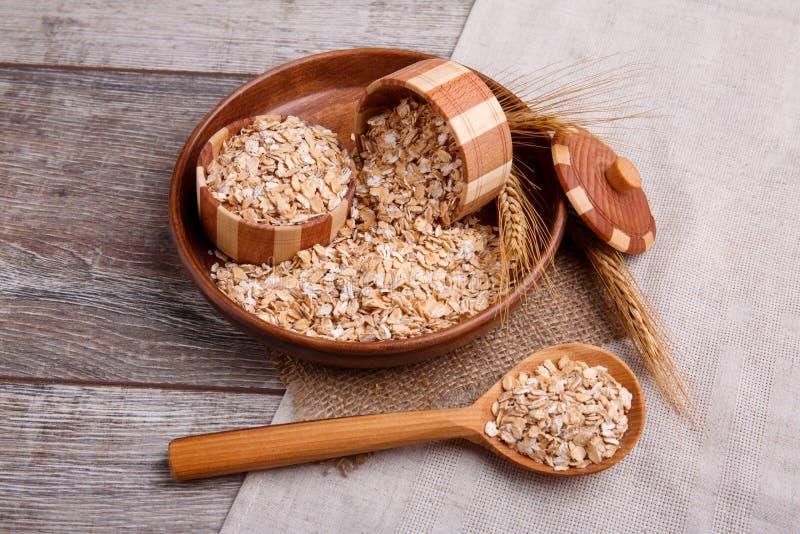 Primo piano della farina d'avena cruda in una ciotola con un cucchiaio di legno pieno della farina d'avena, su una tavola di legn fotografia stock