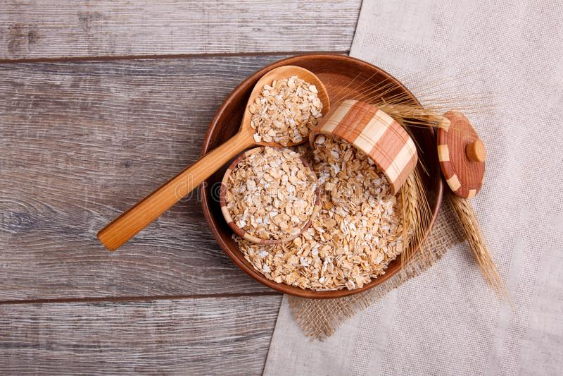 Primo piano della farina d'avena cruda in una ciotola con un cucchiaio di legno pieno della farina d'avena, su una tavola di legn immagine stock