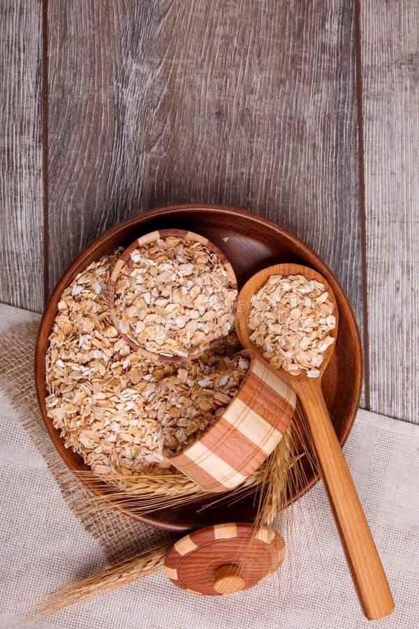 Primo piano della farina d'avena cruda in una ciotola con un cucchiaio di legno pieno della farina d'avena, su una tavola di legn immagini stock