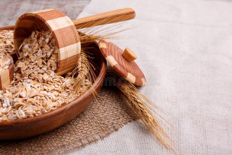 Primo piano della farina d'avena cruda in una ciotola con un cucchiaio di legno su un tovagliolo, su una tavola di legno marrone fotografie stock