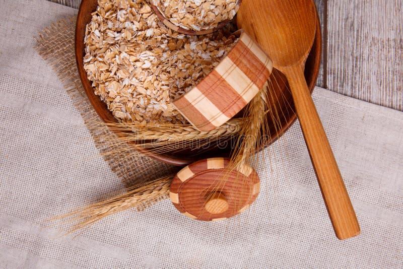 Primo piano della farina d'avena cruda in una ciotola con un cucchiaio di legno su un tovagliolo, su una tavola di legno marrone fotografia stock