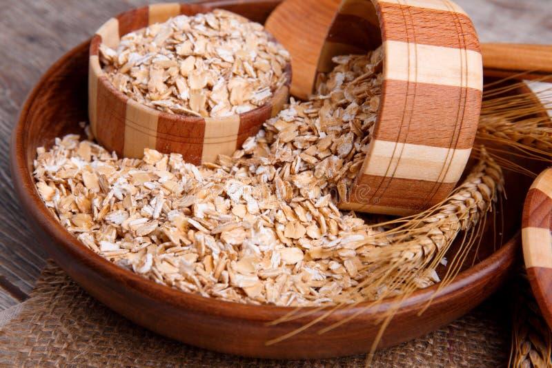 Primo piano della farina d'avena cruda in una ciotola con un cucchiaio di legno su un tovagliolo, su una tavola di legno marrone  immagine stock
