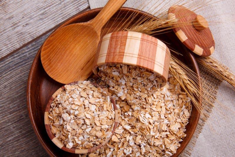 Primo piano della farina d'avena cruda in una ciotola con un cucchiaio di legno su un tovagliolo, su una tavola di legno marrone  fotografia stock libera da diritti