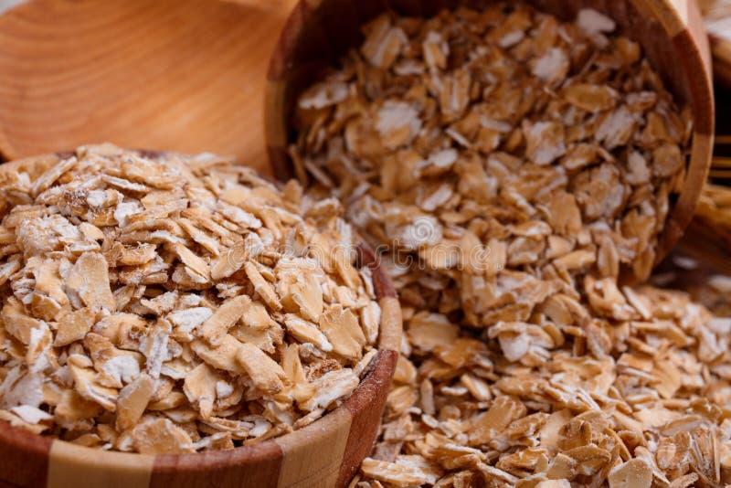 Primo piano della farina d'avena cruda in una ciotola di legno Chiuda sull'immagine immagini stock libere da diritti