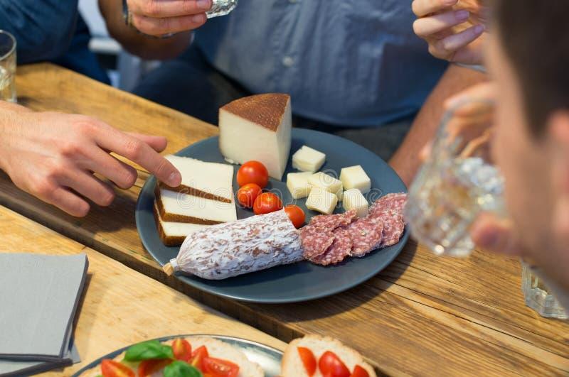 Primo piano della fetta del formaggio di raccolto dell'uomo fotografie stock