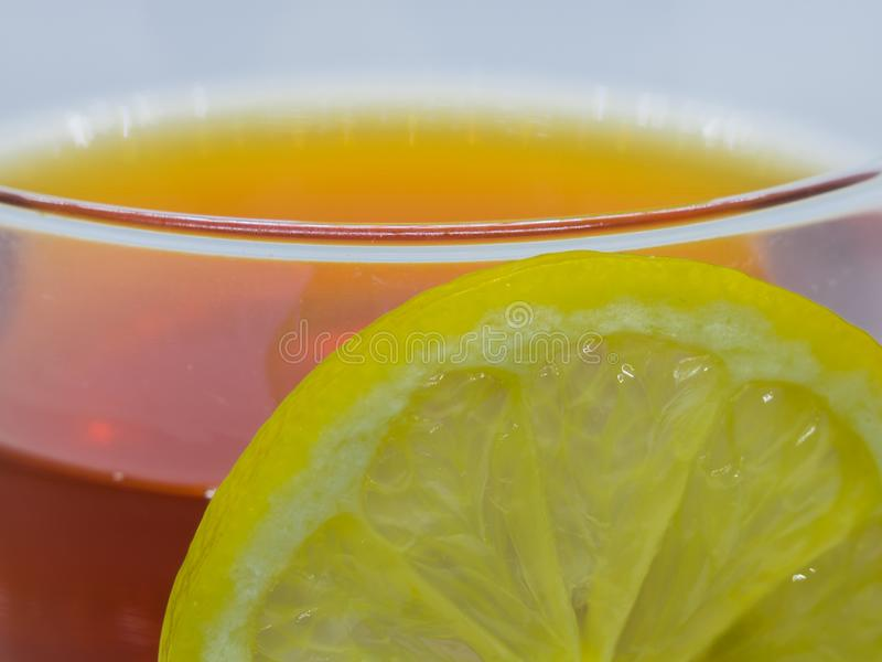 Primo piano della fetta del limone e tazza di tè nero immagini stock libere da diritti