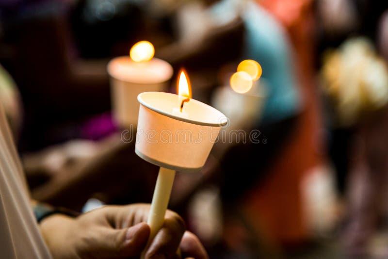 Primo piano della gente che tiene veglia della candela nella speranza di ricerca scura fotografia stock