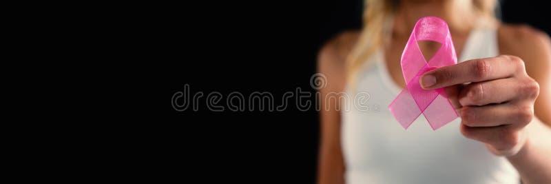 Primo piano della giovane donna che tiene nastro rosa fotografie stock libere da diritti