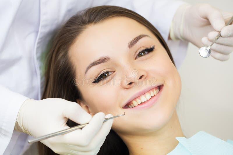 Primo piano della giovane donna durante l'ispezione della cavità orale con aiuto del gancio e dello specchio fotografia stock