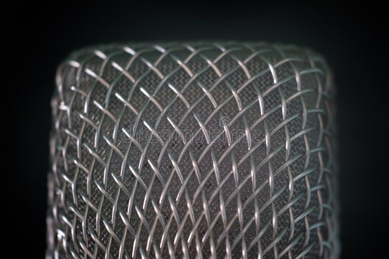 Primo piano della griglia del microfono del filo di acciaio su un fondo nero Macro fucilazione con la profondità di campo bassa I fotografie stock