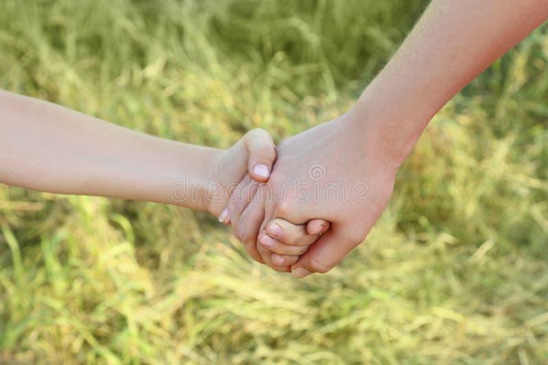 Primo piano della holding del figlio e della madre per le mani immagine stock