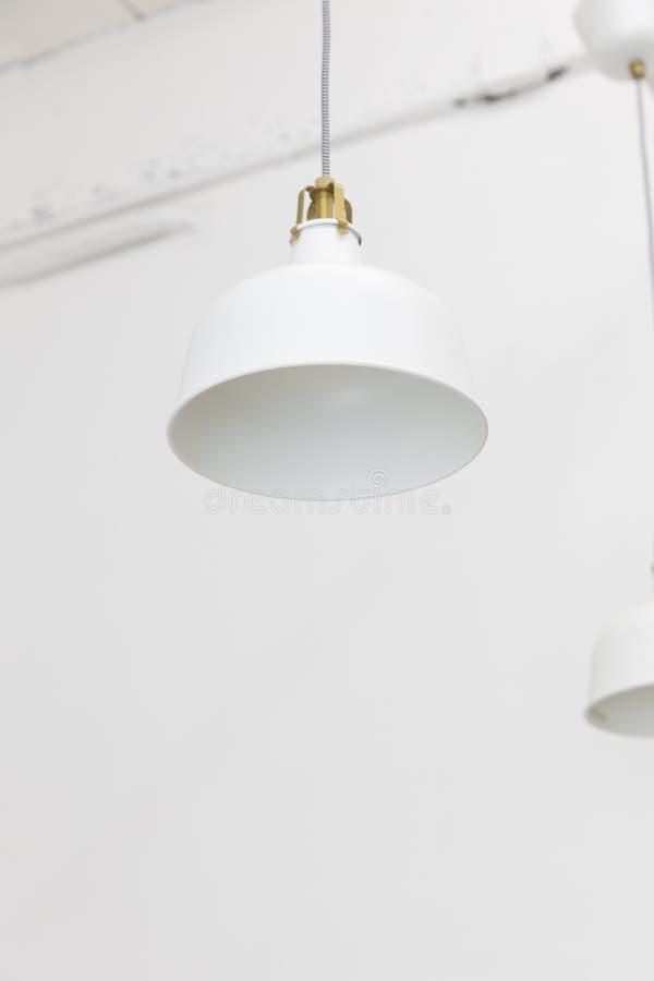Primo piano della lampada bianca d'attaccatura del soffitto sul fondo della parete immagine stock