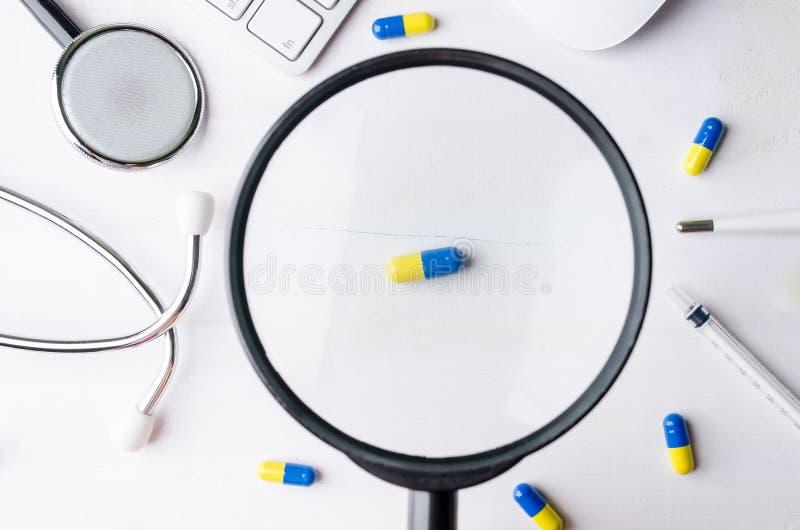 Primo piano della lente d'ingrandimento e della medicina con lo stetoscopio, keyb fotografia stock