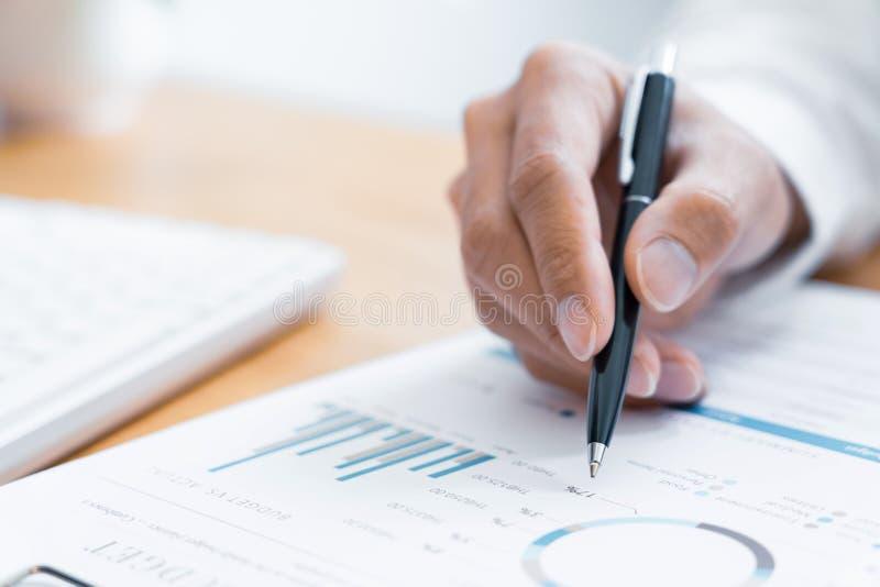 Primo piano della lettura e della scrittura dell'uomo d'affari delle mani con il contratto di firma della penna sopra il document immagini stock