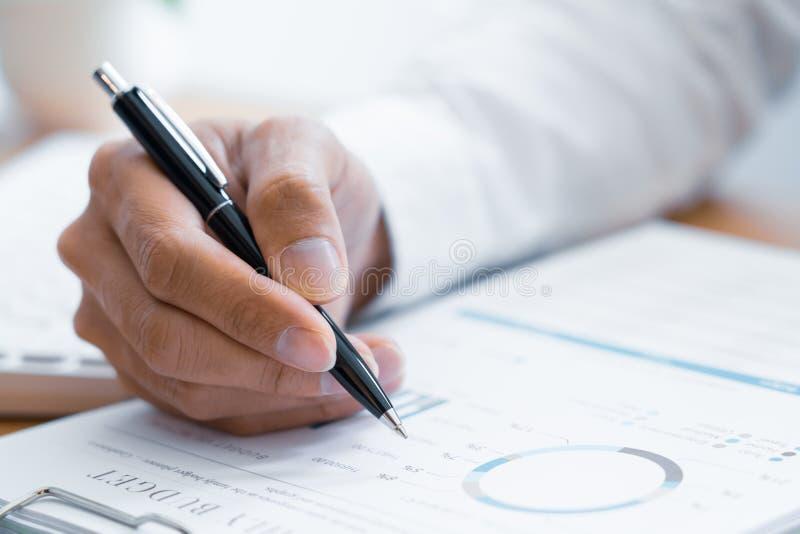 Primo piano della lettura e della scrittura dell'uomo d'affari delle mani con il contratto di firma della penna sopra il document immagine stock libera da diritti