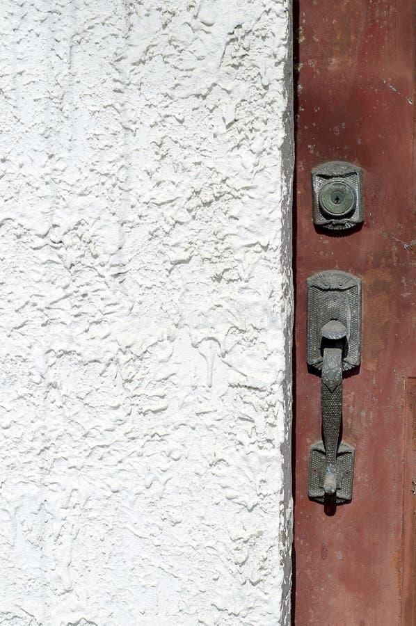 Primo piano della maniglia di porta contro lo stucco bianco immagini stock