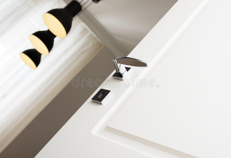 Primo piano della maniglia di porta moderna del cromo Gli elementi di bello interno dell'appartamento immagine stock libera da diritti