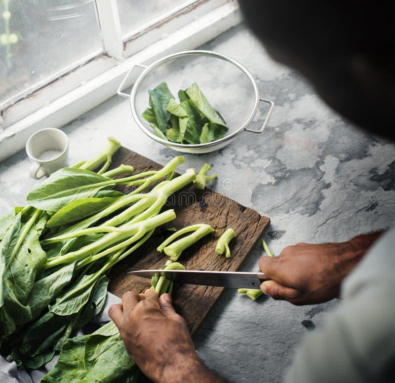 Primo piano della mano con il cavolo di taglio del coltello fotografia stock