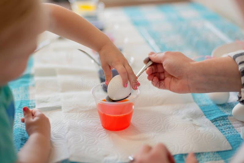 Primo piano della mano del bambino che immerge l'uovo di Pasqua in tintura fotografia stock libera da diritti